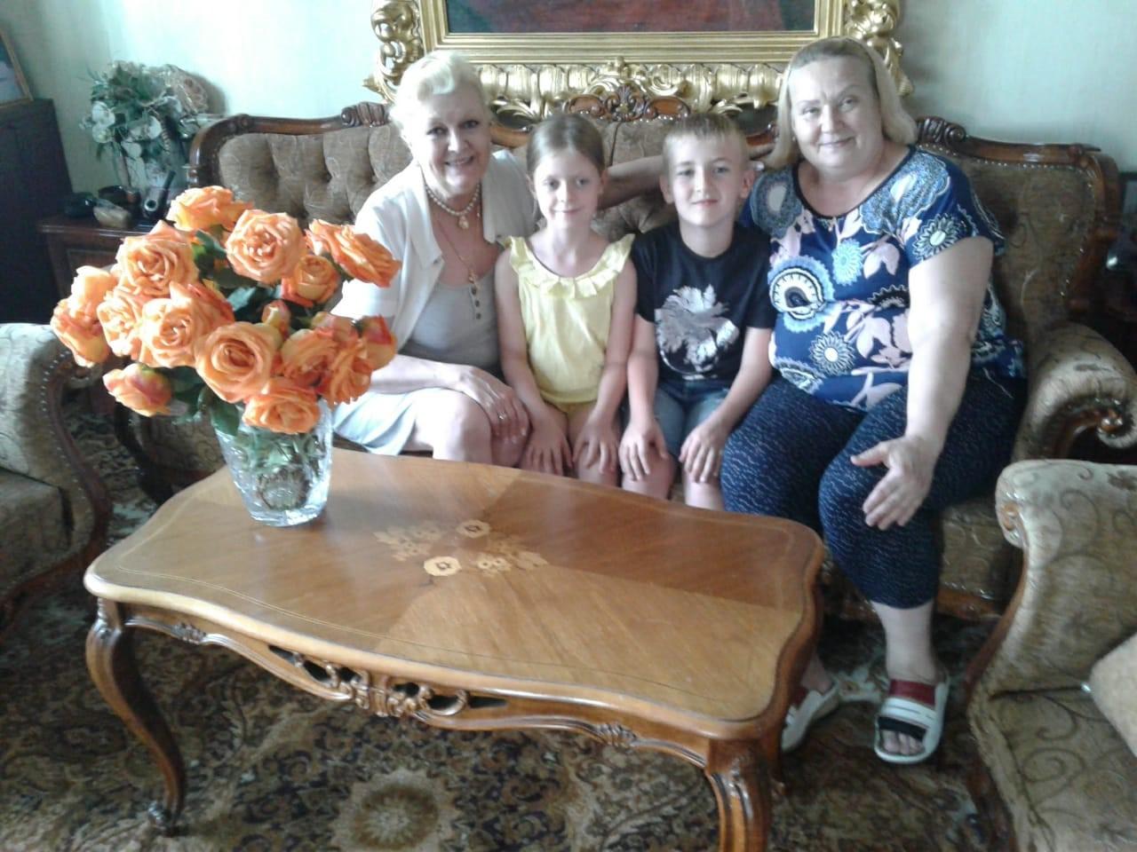 Наталья Дрожжина с помощницей по хозяйству Раисой Ивановной Брослав и ее внуками. Фото: личный архив