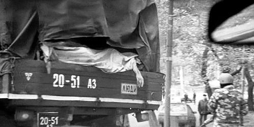 Надпись на борту грузовика «Люди» и безжизненная рука человека
